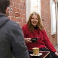 A carer having coffee with another person