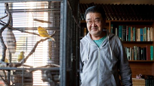 A man looking at birds in a cage